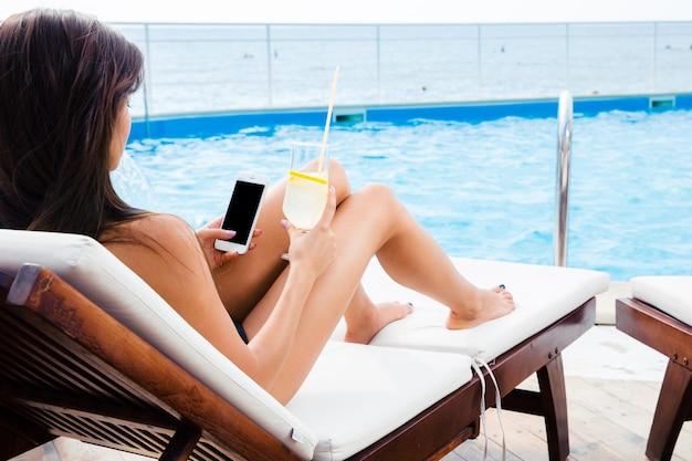 Ritratto di una giovane donna sdraiata sulla sedia a sdraio con smartphone e cocktail all'aperto