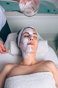 Ritratto di giovane donna sdraiata con gli occhi chiusi che riceve maschera facciale di argilla dall'estetista in spa. medicina, sanità e concetto di bellezza.