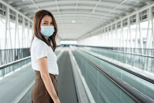 Ritratto di una giovane donna con una maschera medica nel nastro meccanico dell'aeroporto