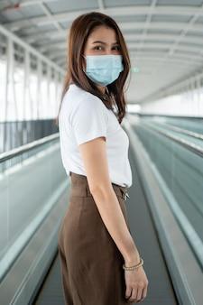 Ritratto di una giovane donna in una maschera medica per la protezione dell'epidemia di malattie infettive pandemiche anti-coronavirus covid-19 nell'area pubblica. concetto di pandemia virale e inquinamento (pm2,5)