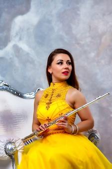 Modello della giovane donna del ritratto in vestito giallo della fase con il flauto nelle mani. strumento a fiato al suonatore di flauto sullo sfondo della parete strutturata. manifesto per la scuola di pubblicità. concept brano musicale o concerto