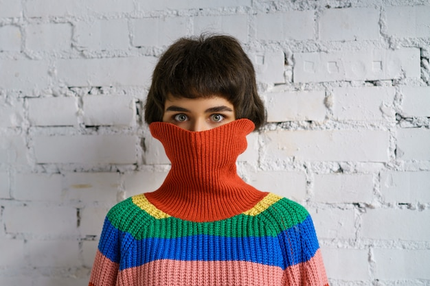 Ritratto di una giovane donna in un maglione multicolore, che copre il viso con un maglione. il concetto di timidezza