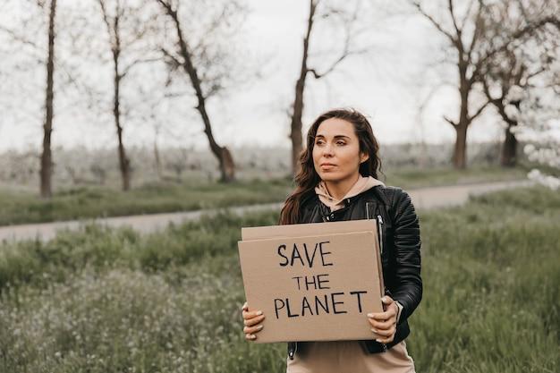 Ritratto di giovane donna in natura che tiene uno striscione con il testo salva il pianeta. femmina con striscioni che protestano per l'inquinamento e il riscaldamento globale nella foresta per salvare il pianeta terra. concetto di mondo
