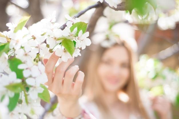 Ritratto di una giovane donna vicino a un albero in fiore.