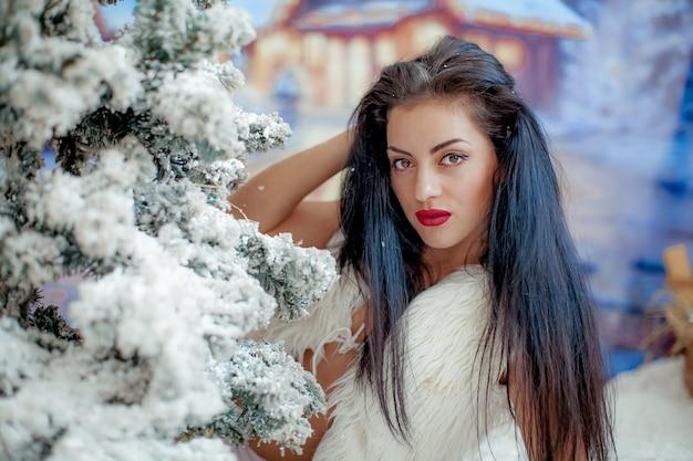 Ritratto di una giovane donna vicino ad un albero di natale