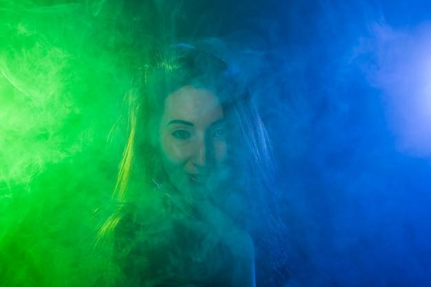 Ritratto di giovane donna in neon blu e verde fumo con vape o sigarette elettroniche.