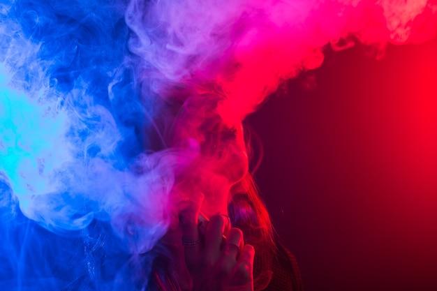 Ritratto di giovane donna in neon rosso e blu fumo con vape o sigarette elettroniche.