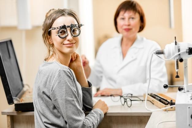 Ritratto di una giovane donna paziente con oculista senior durante la consultazione in ufficio