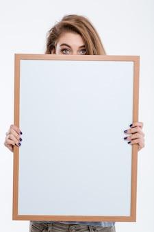 Ritratto di una giovane donna che fa capolino su un bordo bianco isolato su uno sfondo bianco