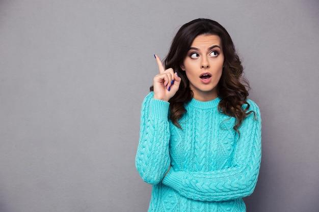 Ritratto di una giovane donna che punta il dito su un muro grigio