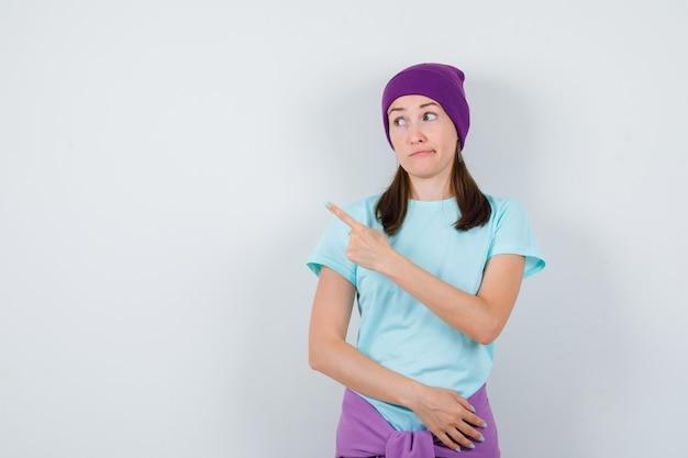 Ritratto di giovane donna che indica nell'angolo in alto a sinistra in maglietta, berretto e guardando indecisa vista frontale
