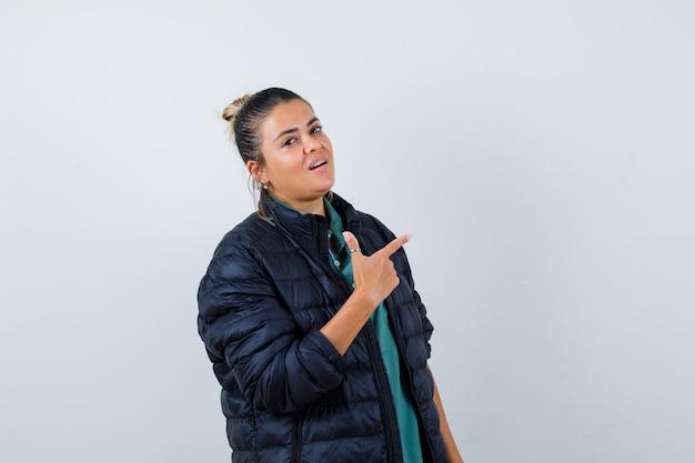 Ritratto di giovane donna che punta all'angolo in alto a destra in giacca imbottita e guarda fiduciosa vista frontale