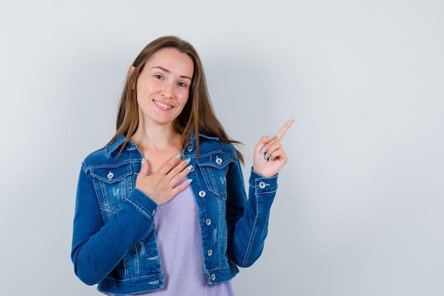 Ritratto di giovane donna che indica nell'angolo in alto a destra, con la mano sul petto in maglietta, giacca e guardando grato vista frontale