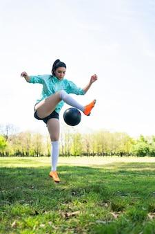 Ritratto di giovane donna praticando abilità di calcio e facendo trucchi con il pallone da calcio. giocatore di calcio che manipola la palla. concetto di sport.