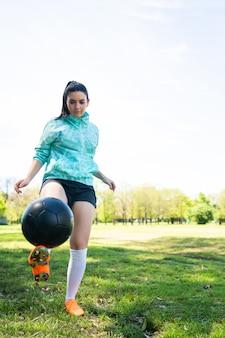 Ritratto di giovane donna praticando abilità di calcio e facendo trucchi con il pallone da calcio. giocatore di calcio che manipola la palla.