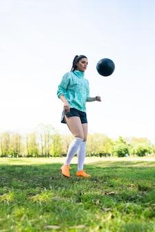 Ritratto di giovane donna praticando abilità di calcio e facendo trucchi con il pallone da calcio.