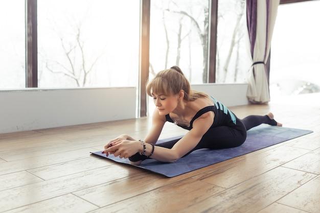 Ritratto di giovane donna che pratica yoga al coperto vicino alla grande finestra