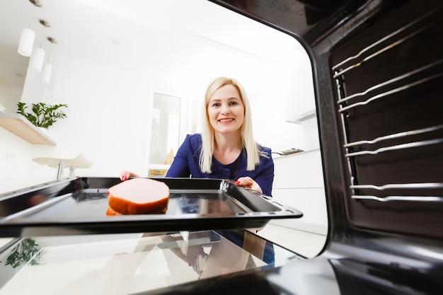 Ritratto di una giovane donna che prepara il cibo in cucina. la giovane casalinga tiene in mano carne appena sfornata