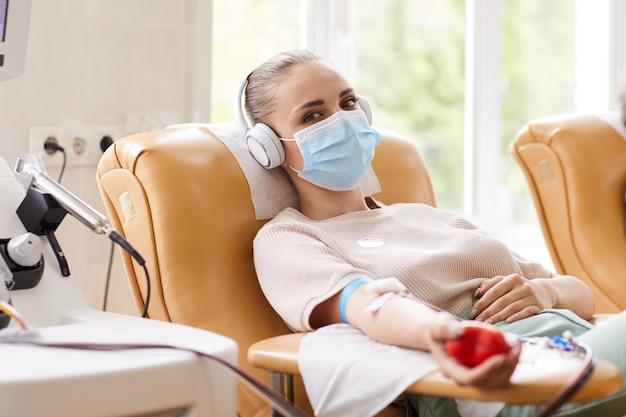 Ritratto di giovane donna in maschera protettiva mentre giaceva sul divano e riceve una trasfusione di sangue in ospedale