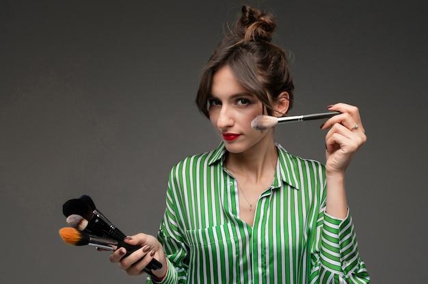 Ritratto di giovane donna che mette sul trucco in blusa a strisce con le spazzole di trucco in sue mani isolate