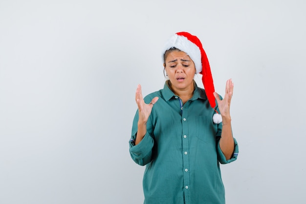 Ritratto di giovane donna che alza le mani, guarda in basso in camicia, cappello di babbo natale e sembra sconvolta vista frontale