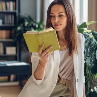 Ritratto del libro di lettura della giovane donna a casa.