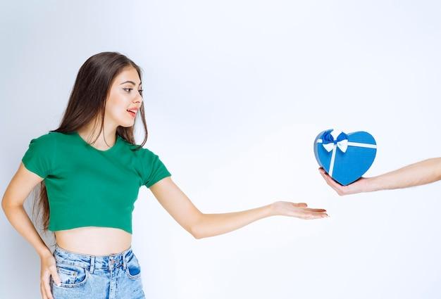 Ritratto di giovane donna che riceve confezione regalo blu da qualcuno su sfondo bianco.