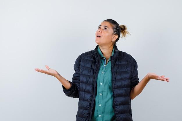 Ritratto di giovane donna che mostra gesto impotente, alzando lo sguardo in camicia, piumino e guardando la vista frontale premurosa