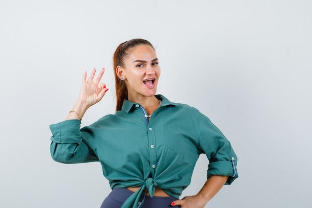 Ritratto di giovane donna che mostra gesto ok in camicia verde e sembra allegra vista frontale