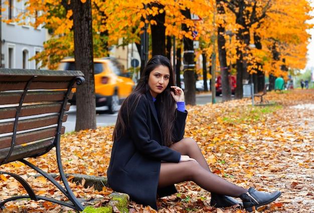 Ritratto di una giovane donna seduta nel parco in autunno