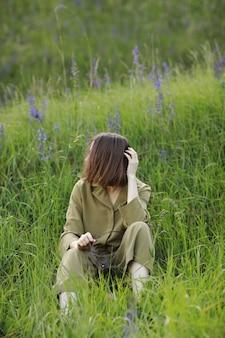 Ritratto di una giovane donna seduta in un campo sull'erba primaverile tra fiori viola. la ragazza alla moda gode del clima primaverile soleggiato. bellezza naturale di una donna, cosmetici naturali