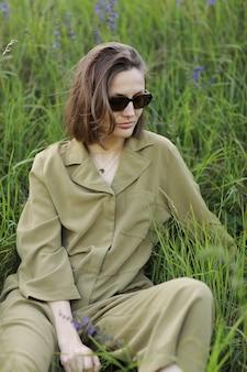 Ritratto di una giovane donna seduta in un campo sull'erba primaverile tra fiori viola. ragazza alla moda che indossa occhiali da sole gode di un clima primaverile soleggiato. bellezza naturale di una donna, cosmetici naturali.