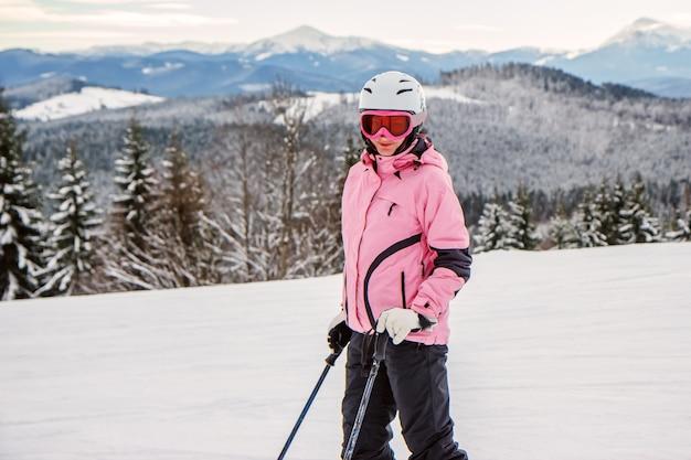 Ritratto di una giovane donna in un completo da sci e casco nelle montagne innevate
