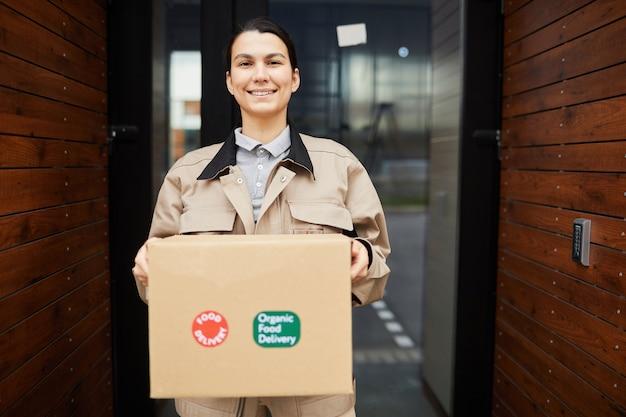 Ritratto di giovane donna che sorride alla macchina fotografica mentre tiene il pacco che consegna cibo da asporto