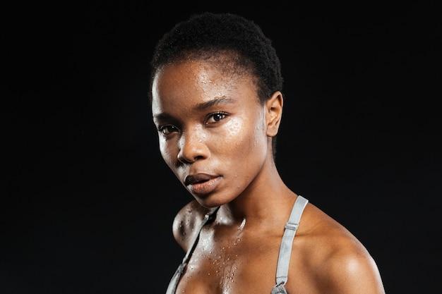 Ritratto di una giovane donna in abbigliamento sportivo isolato sul muro nero