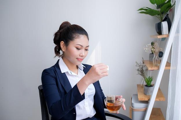 Ritratto di giovane donna in piedi con una tazza di tè in ufficio