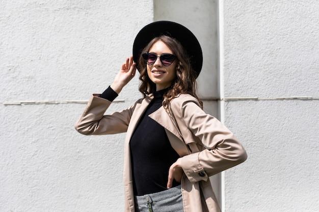 Ritratto di una giovane donna in occhiali da sole e cappello nero che cammina per strada.