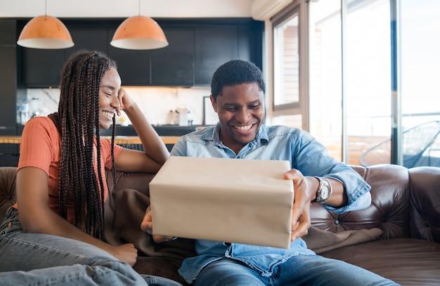 Ritratto di giovane donna che sorprende il suo fidanzato con una confezione regalo.