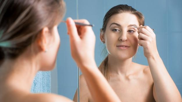 Ritratto di giovane donna che si prende cura delle sue sopracciglia con una pinzetta in bagno.
