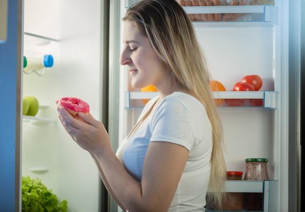Ritratto di giovane donna che prende la ciambella dal frigorifero di notte