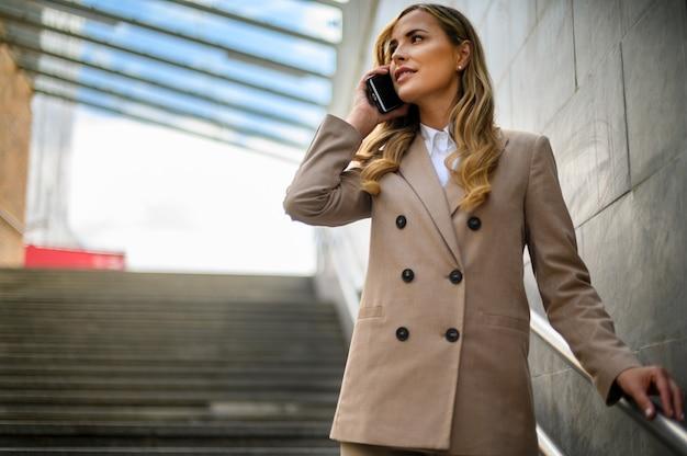 Ritratto di una giovane donna che parla al telefono su scale all'aperto