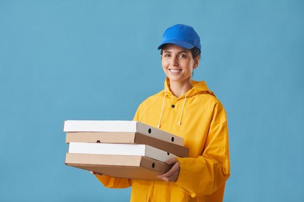 Ritratto di giovane donna in uniforme tenendo la pizza e sorridente sul blu