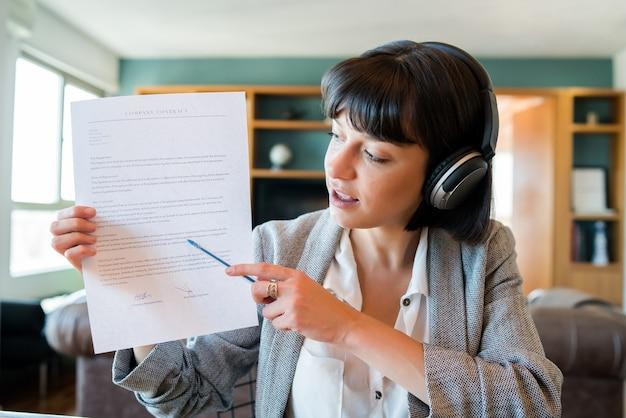 Ritratto di giovane donna in videochiamata e mostrando qualcosa sulla carta. donna d'affari che lavora da casa. nuovo stile di vita normale.
