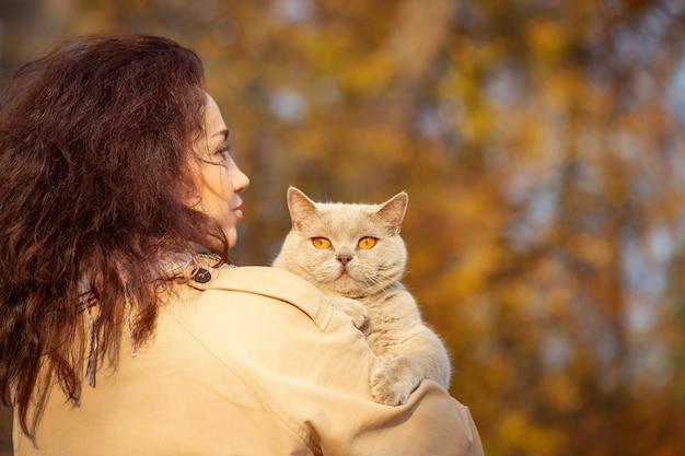 Ritratto di una giovane donna che cammina nel parco autunnale con un gatto tra le braccia sera