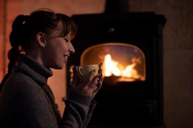 Ritratto di giovane donna in un maglione caldo che beve bevanda calda dalla tazza davanti al caminetto