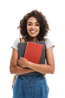 Ritratto di giovane donna che indossa uno zaino sorridente e tiene quaderni isolati su muro bianco