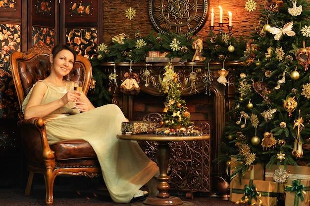 Ritratto di giovane donna che indossa un bellissimo abito dorato seduto in poltrona vintage