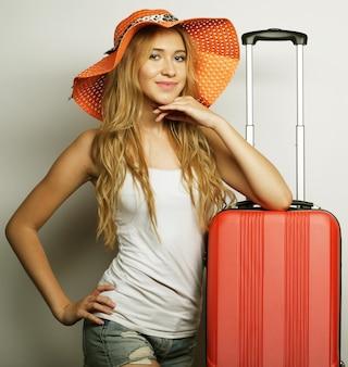 Ritratto di giovane donna che indossa un grande cappello di paglia arancione in piedi con una borsa da viaggio arancione