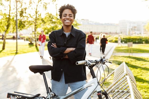 Ritratto di giovane donna che indossa abiti casual in piedi con la bicicletta mentre si cammina nel parco cittadino