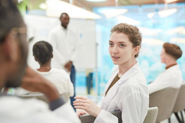 Ritratto di giovane donna che indossa camice da laboratorio mentre parla con l'uomo durante il seminario medico, copia spazio
